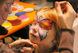 Художник раскрашивает лицо ребенку